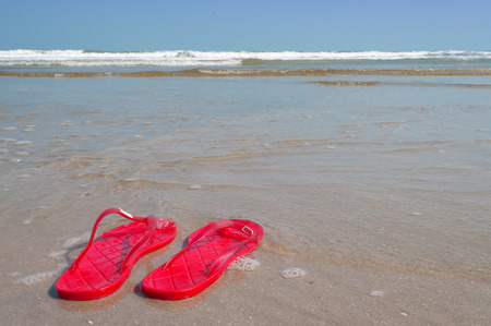 Red sandals on the sand near sea.