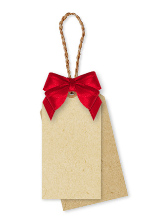 Brown Paper tag, rope and red ribbon bow on white background. Banco de Imagens