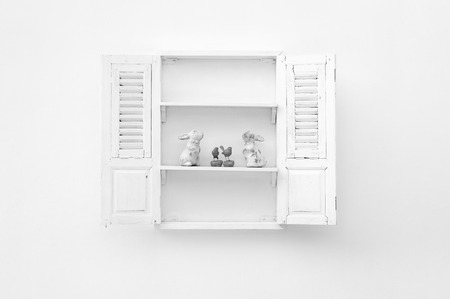 White window on a white wall with wooden floor put white rabbits and birds.