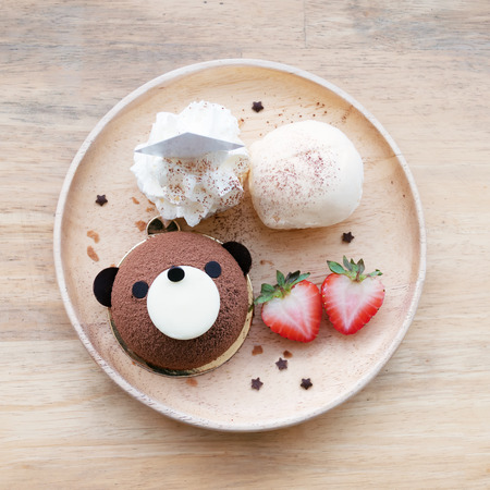 Bear chocolate cake with  ice cream, white cream and strawberries on wooden plates.