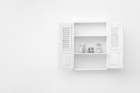 White window on a white wall with wooden floor put white rabbit and bird. Banco de Imagens