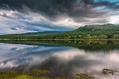 landscape of green forest mountain and storm cloud reflect on water in rainy season Banco de Imagens