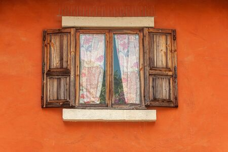 Vintage brown wooden window on orange cement wall