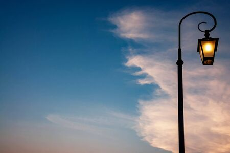 Retro style street lamppost at twilight against cloud and blue sky Фото со стока