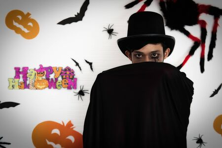 Asian men make-up and dress in Dracula for Halloween festival. He stood and covered the face with horror, spiders, bats, and pumpkin on the behind. Imagens