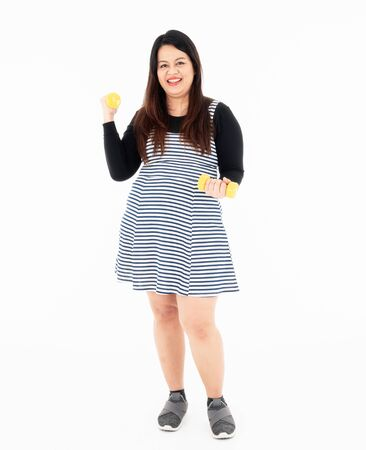 Fat young beautiful woman is exercising by lifting yellow dumbbells with both hands. She smiles and enjoys losing weight for her good health. Isolated on a white background.