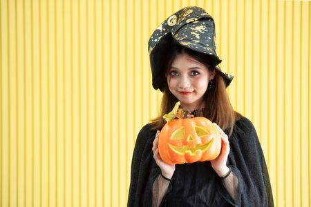 An Asian beautiful woman model dressed as a witch and a witch's hat costume smile and acting on Halloween party standing with a pumpkin on hand with yellow background.
