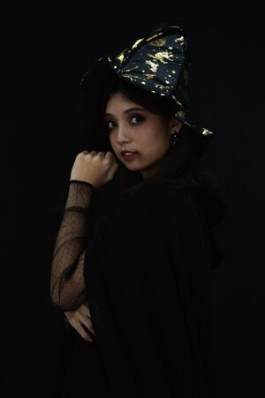 An Asian beautiful woman model dressed as a witch and a witch's hat costume smile and acting on Halloween party with dark background. copy space