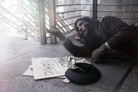 The lives of the homeless or beggar are sad, dirty, poor, hungry, tired, fear and want to have a home, clothes, food, and money. Man waits for an opportunity from the person to help them.