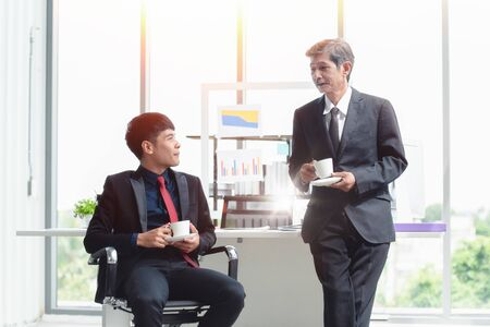Two businessmen in the modern office have coffee cup are analyzing, brainstorming, talking and discuss information about their work.