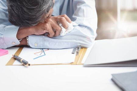 The businessman sat down at the desk in the office with a tissue on hand after the stock market sale report failure. He was tired, crying and frustrated. Business concept. Overworked and Sleeping.