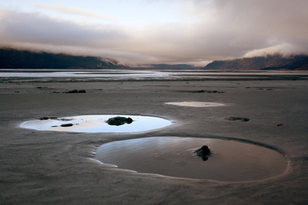Serene Puddle Formations on Cold Sandy Remote Beach