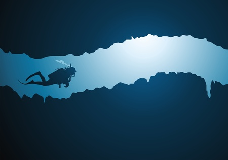 underwater light: The diver floats on a narrow underwater tunnel