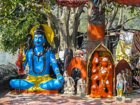 India. The holy city of Haridwar. Clay figure of Lord Shiva. On the banks of the Ganges river under a tree standing sculptures of the Gods.