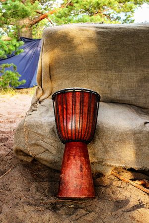 Traditional African ethnic musical percussion instrument Jumbo drum. Esoteric yoga festival on the sandy beach of the Gulf of Finland.