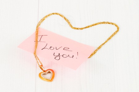 gold jewelry in the shape of a heart on white boards photo