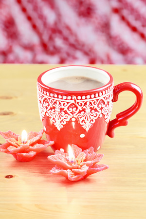 Cup of hot cocao with red poinsettia candle photo