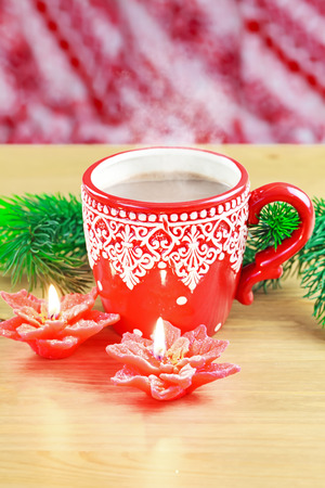 Cup of hot cocao with red poinsettia candle and pine photo