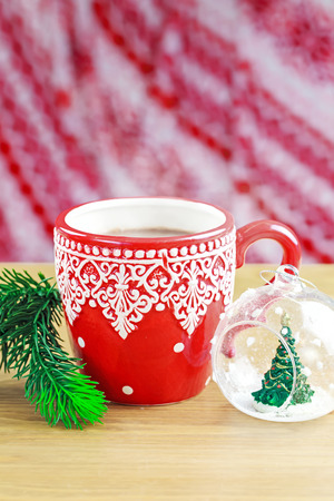 Cup of hot cocao with christmas glass toy and pine photo