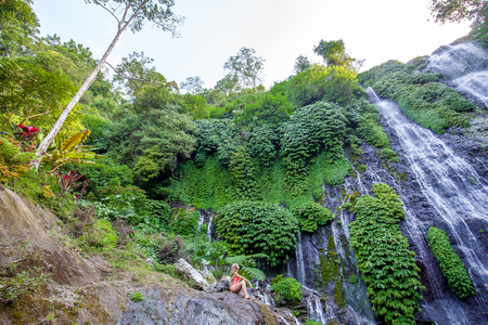 Young woman with long hair in pink swimsuit sitting on the rock near Banyumala twin waterfalls with cascades among green tropical trees and plants on the north of Bali island, Indonesia