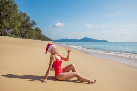 Happy young woman with long hair in red swimsuit and santa claus hat show v sign gesture sitting on the wide empty tropical beach near the sea with blue water and sky on Phuket island, Thailand