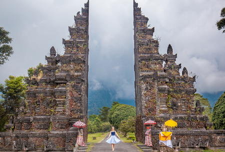 Young woman with long hair dressed in skirt standing at traditional Hindu temples gate (Gapura Handara Kosaido) on the north of Bali island, Indonesia