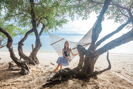 Young happy girl sitting in the hammock between green trees on the tropical beach near the sea