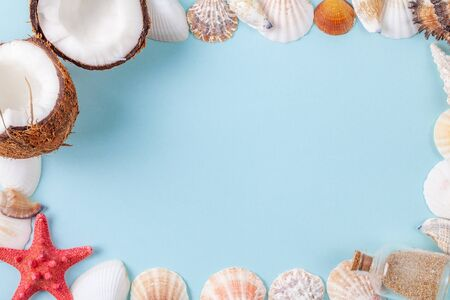 Flat lay frame composition with beautiful starfishes, sea shells, coconut and bottle with sand on a blue background