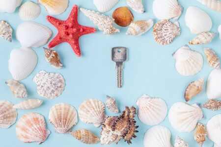 Key on a blue summer background with different shells and starfish