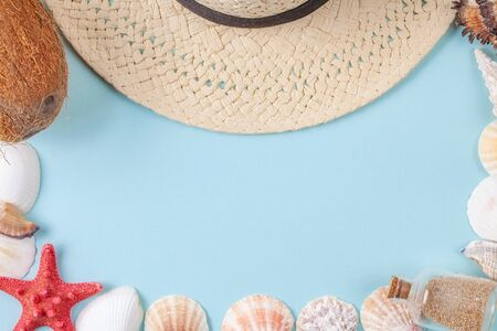 Flat lay composition with beautiful starfishes, sea shells, coconut, bottle with sand and straw hat on a blue background