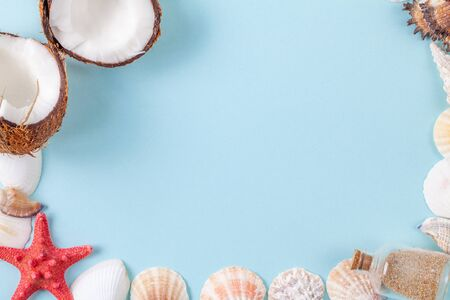 Flat lay composition with beautiful starfishes, sea shells, coconut and bottle with sand on a blue background