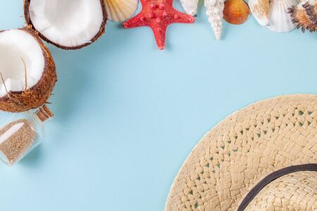 Flat lay composition with beautiful starfishes, sea shells, coconut, straw hat and bottle with sand on a blue background