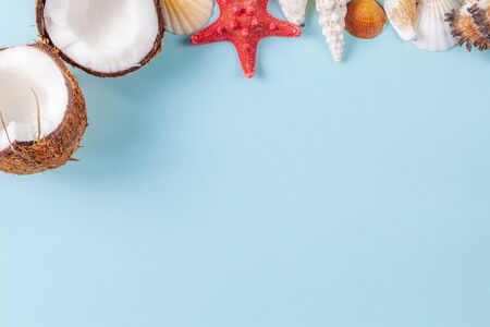 Flat lay composition with beautiful starfishes, sea shells and coconut on a blue background