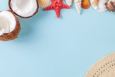 Flat lay composition with beautiful starfishes, sea shells, straw hat and coconut on a blue background