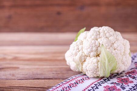 Raw cauliflower on wooden background