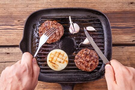 Fried burger beef cutlets on grill pan on wooden background with mens hands Reklamní fotografie