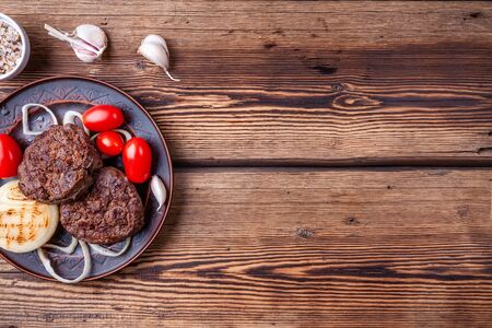 Tasty grilled burger meat with vegetables on wooden background with salt, garlic