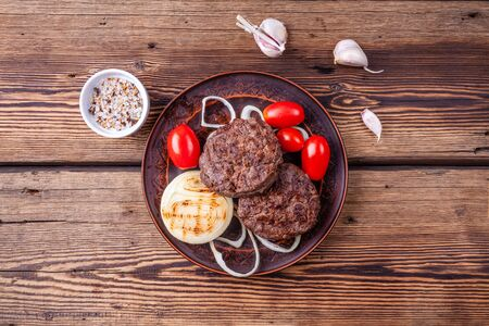 Roasted burger meat with vegetables on plate on wooden background with salt
