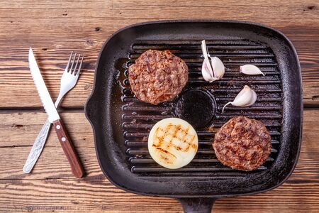 Fried burger beef cutlets with onion and garlic on grill pan with fork and knife