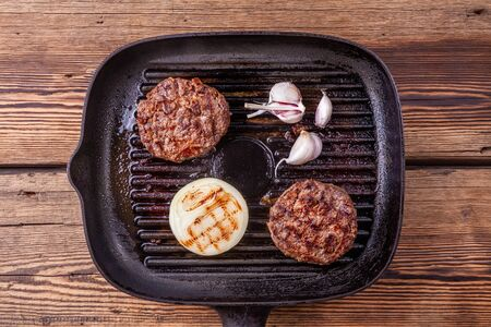Fried burger beef cutlets with onion, garlic on grill pan on wooden background