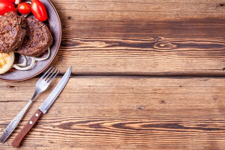 Grilled beefsteaks with onions and tomatoes on plate with fork and knife