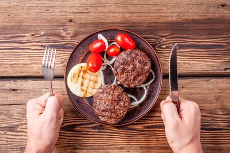 Cooked burger meat on wooden background with mens hands with fork and knife