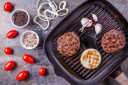 Fried burger beef cutlets with vegetables on grill pan on gray marble background Reklamní fotografie