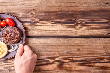 Tasty roasted burger meat with vegetables on wooden background with mans hand