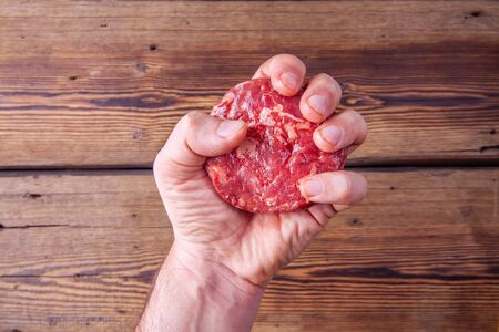 Adult mans arm firmly holding a raw beef burger meat on a wooden background Reklamní fotografie