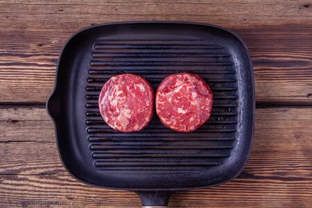 Top view of two raw beef burger meats on grill pan on a wooden background