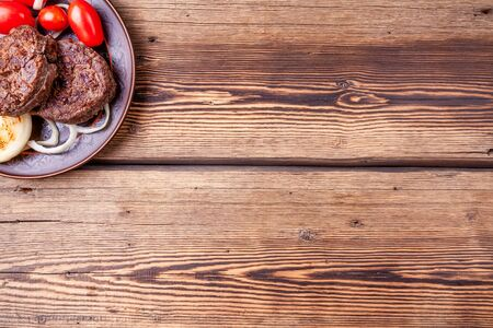 Tasty grilled burger meat with onions and tomatoes on wooden background Reklamní fotografie