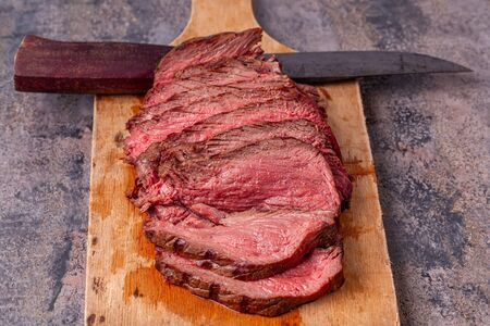 Roast beef slices on wooden cutting board with old knife