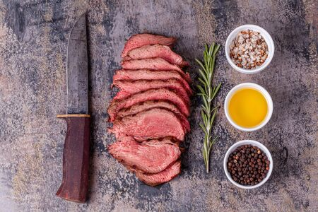 Slices of roast beef with rosemary, salt, pepper and olive oil Reklamní fotografie