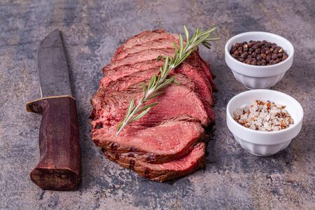Slices of roast beef with rosemary, salt snd pepper on grey marble background